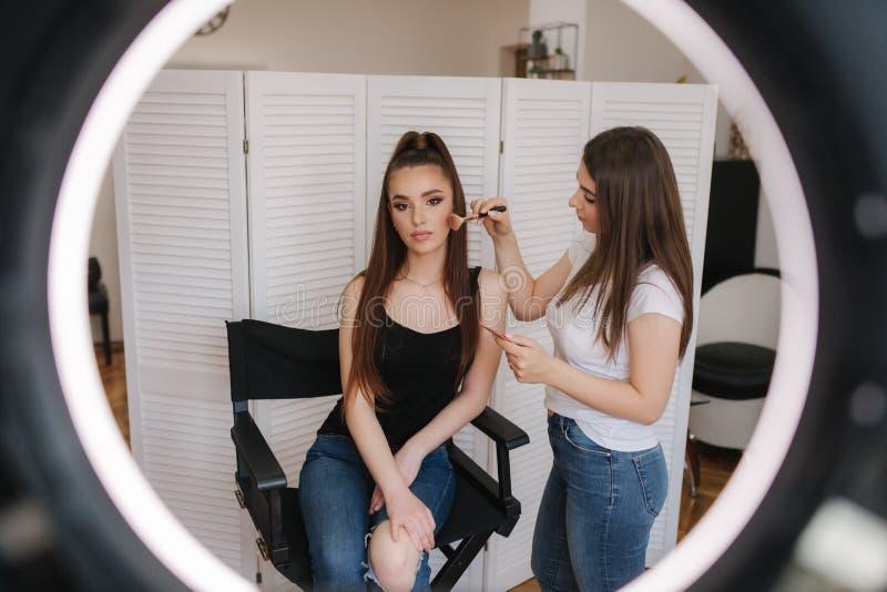 Foto fast cirkellampan av makeupkonstnären som gör en makeup för attraktiv ung flicka Bakgrund av vit vikning arkivfoto