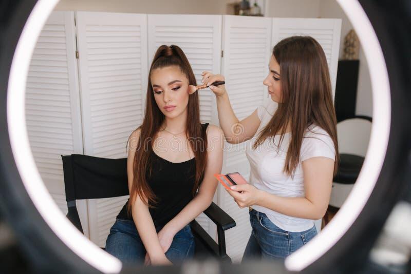 Foto fast cirkellampan av makeupkonstnären som gör en makeup för attraktiv ung flicka Bakgrund av vit vikning royaltyfria foton