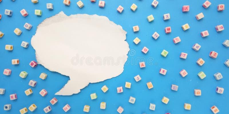 Foto-flache Lage, blauer Hintergrund und Alphabet-Plastikwürfel-Perlen-Element-Entwurfs-und Blasen-Schwätzchen für Mitteilung, stockfotos