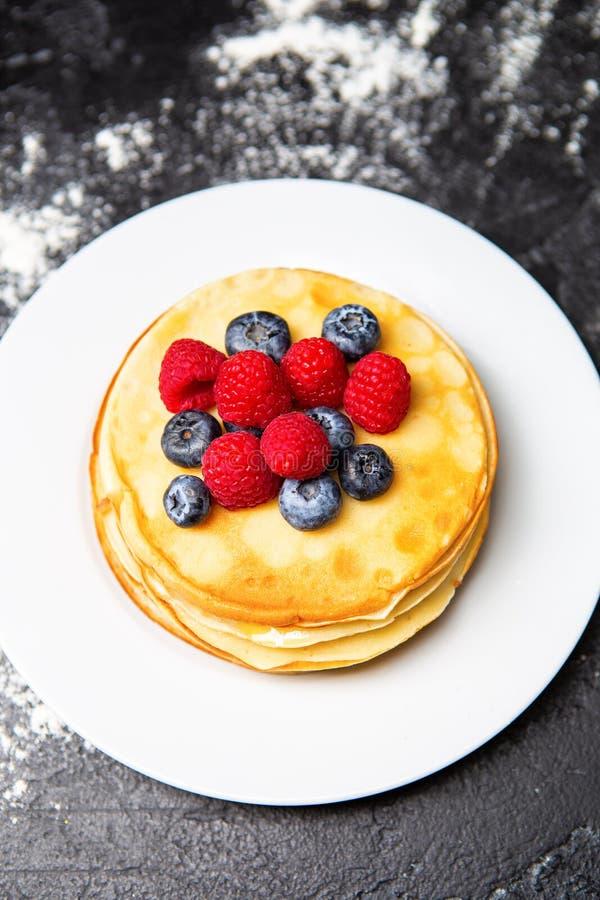 Foto från överkant av plattan med pannkakor, blåbär, hallon royaltyfri foto