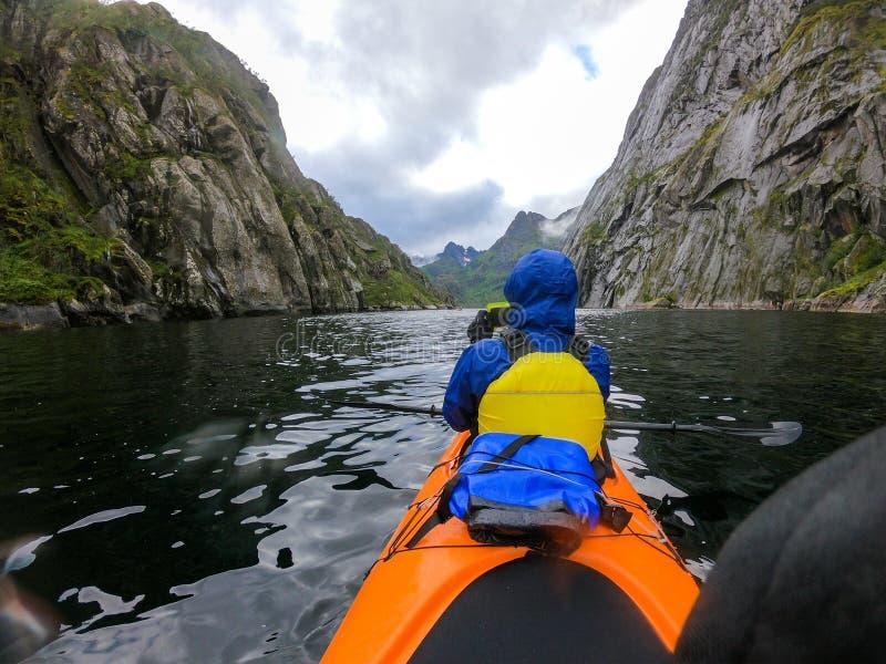 Foto från baksida av den kvinnliga turisten med skovelkanoten som svävar längs floden royaltyfri fotografi