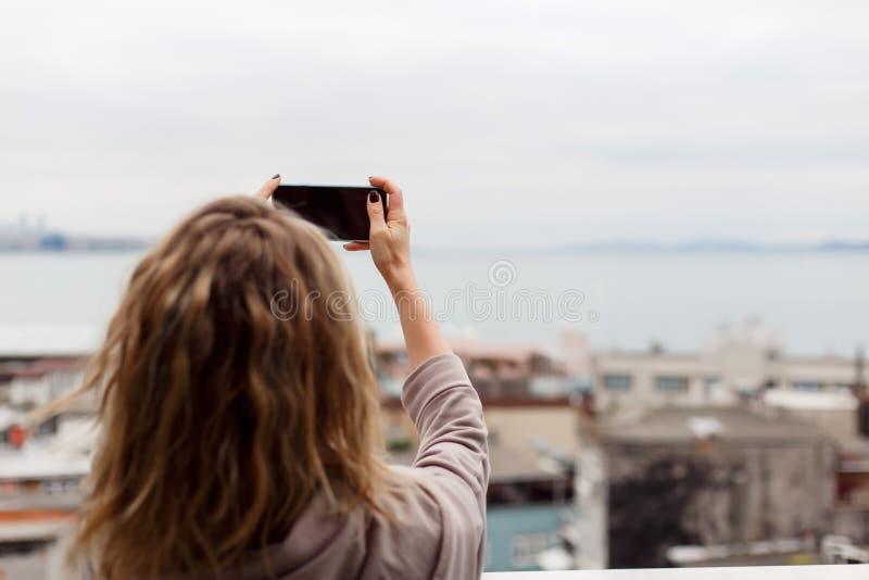 Foto från baksida av den lockiga blonda tagande bilden av själv mot suddig bakgrund arkivfoton