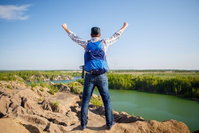 Foto från baksida av den unga turisten med ryggsäcken med händer upp mot bakgrund av berglandskapet, sjö fotografering för bildbyråer
