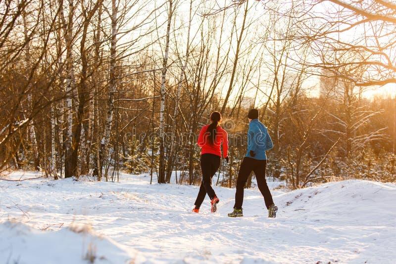 Foto från baksida av idrottskvinnan och idrottsmannen på inkörd vinter för morgon arkivfoton