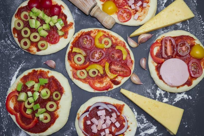 Foto från ovannämnt av framställning av mini- pizzamatlagningprocess Liten personlig snabb miniatyrpizza med ost, tomater och avo fotografering för bildbyråer