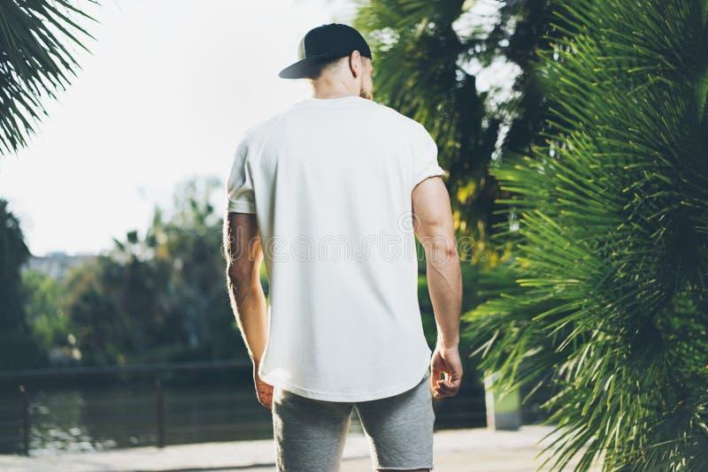 Foto Gebaarde Spiermens die Witte Lege t-shirt dragen, snapback GLB en borrels in de zomertijd Het groene Park van de Stadstuin stock foto's