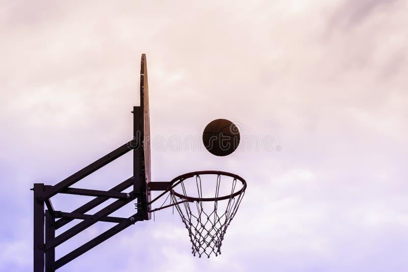 Foto gráfica del escudo del baloncesto, bola que vuela a la cesta en el fondo del cielo Concepto de deporte, exactitud golpeada c fotografía de archivo libre de regalías