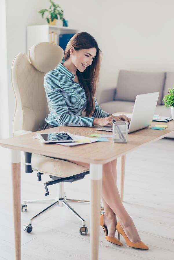 Foto a grandezza naturale di signora elegante di affari che si siede nel suo ufficio a immagini stock libere da diritti