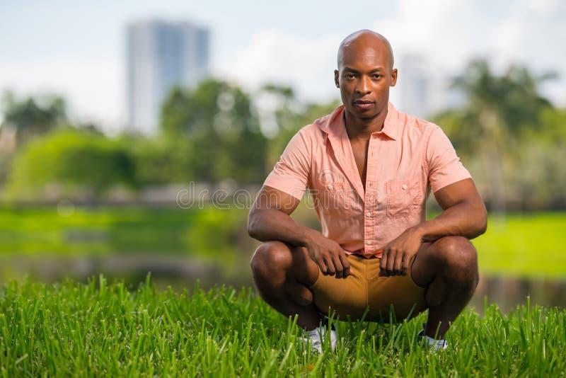 Foto-hübscher junger Afroamerikanermann, der auf Gras im Park hockt Ausdrucksloser Ausdruck, der tief in die Kamera anstarrt stockbild