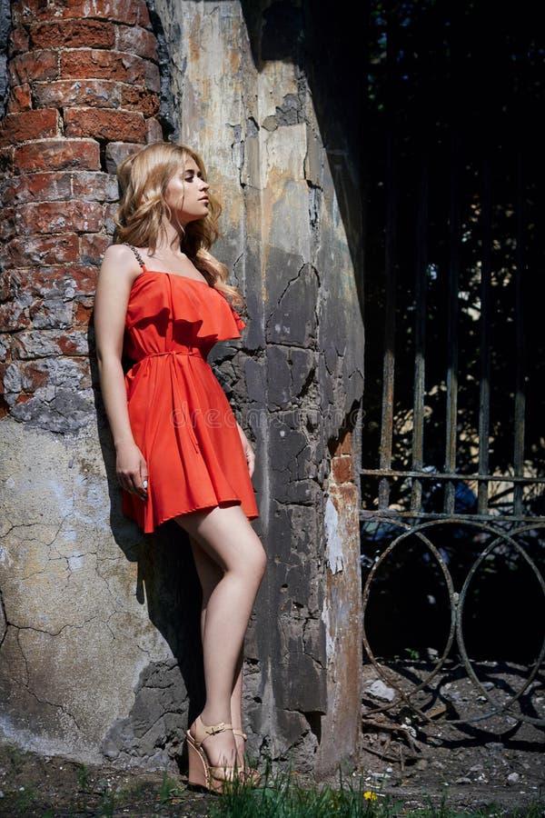 Foto hermosa de la mujer joven de la moda al aire libre cerca del viejo verano de la GRANJA Blondes de la muchacha del retrato en imagen de archivo libre de regalías