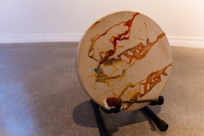 Foto hermosa de un tambor sagrado colorido del nativo americano en piso concreto imagen de archivo