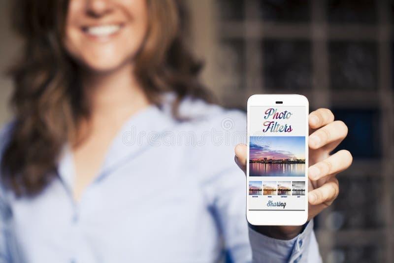 Foto het uitgeven software app in een mobiele telefoon Vrouwenholding het in de hand royalty-vrije stock foto's