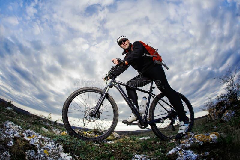 Foto hieronder van de bergfietser in de zwarte sportwear op de rotsen tegen dramatische hemel met wolken royalty-vrije stock fotografie