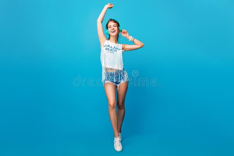 Foto integral de la muchacha bonita con el baile largo del pelo rizado en fondo azul en estudio Ella lleva T-shir blanco imagen de archivo