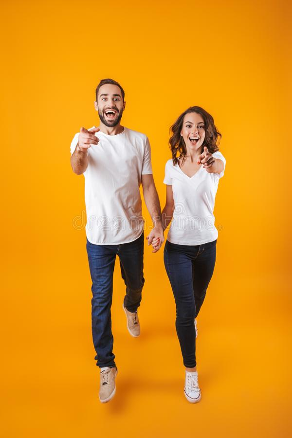 Foto integral de los pares alegres que llevan a cabo las manos mientras que camina, aislada sobre fondo amarillo fotografía de archivo