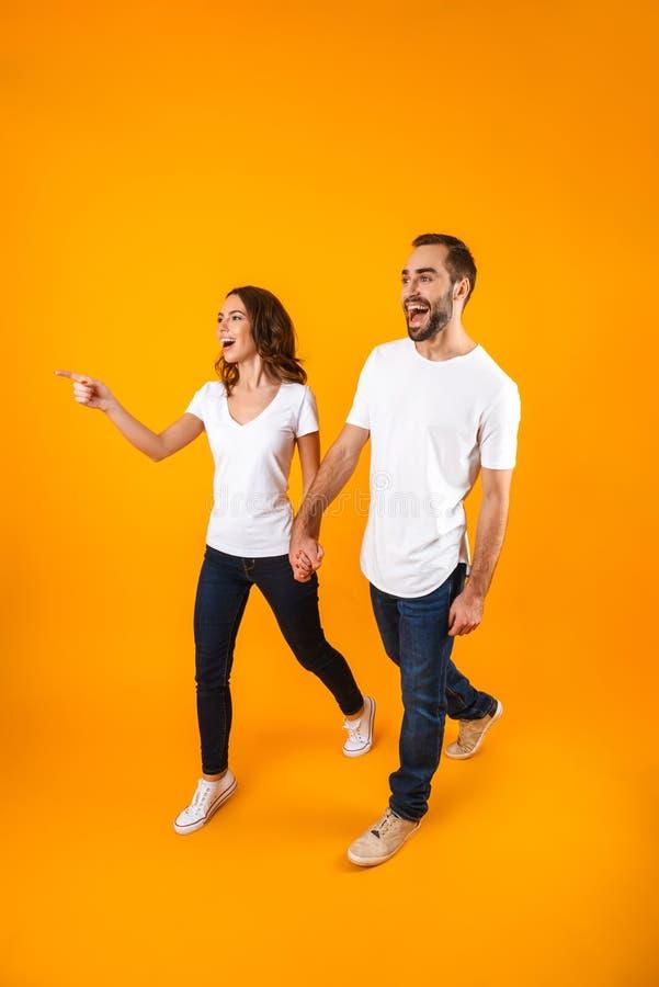 Foto integral de los pares atractivos que sonríen y que caminan, sobre fondo amarillo imagen de archivo
