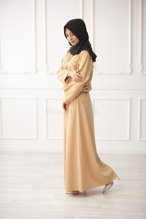 Foto integral de una muchacha hermosa del aspecto medio-oriental, cerrada en el traje verde y el pañuelo musulmán negro en su hea foto de archivo