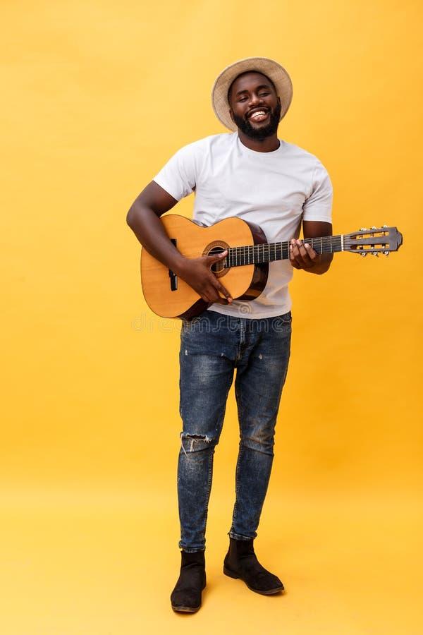 Foto integral del hombre artístico emocionado que toca su guitarra Aislado en fondo amarillo fotografía de archivo