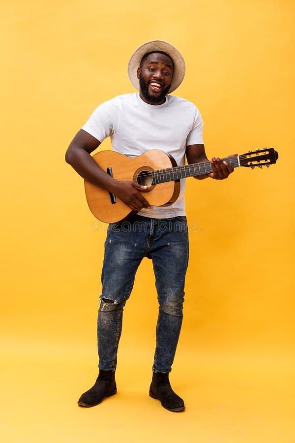 Foto integral del hombre artístico emocionado que toca su guitarra en la habitación casual Aislado en fondo amarillo fotos de archivo libres de regalías