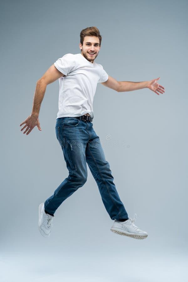 Foto integral del hombre divertido en la camiseta casual, la chaqueta y los vaqueros corriendo o saltando en el aire aislado sobr imagen de archivo