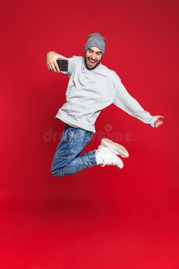 Foto integral del hombre hermoso que salta y que toma la foto del selfie en el teléfono celular aislado sobre fondo rojo foto de archivo