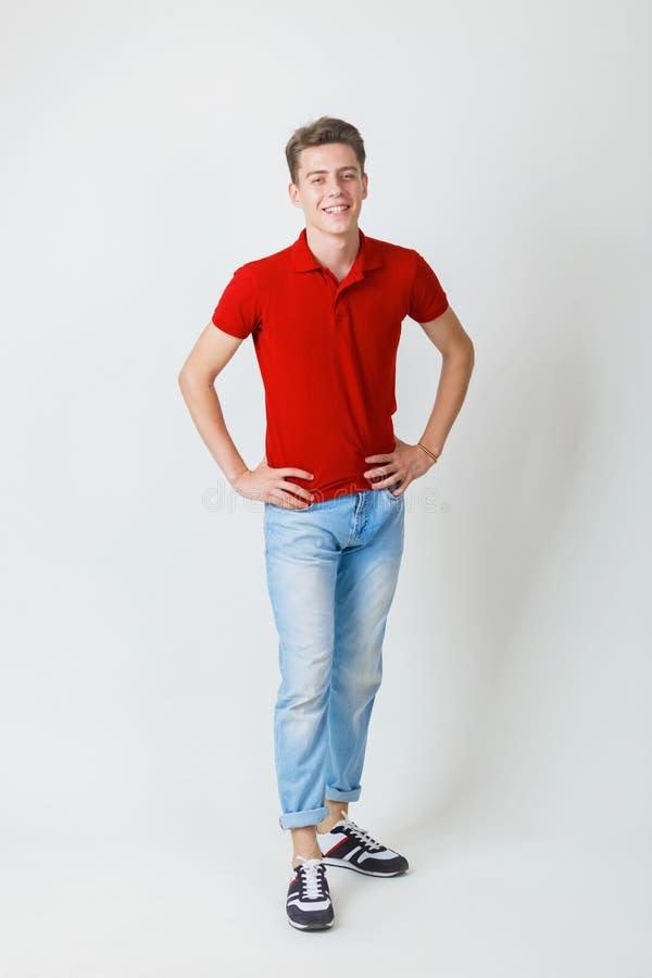 Foto integral del individuo europeo alegre de mirada amistoso que lleva la camisa roja y la situación sonriente de los tejanos so foto de archivo
