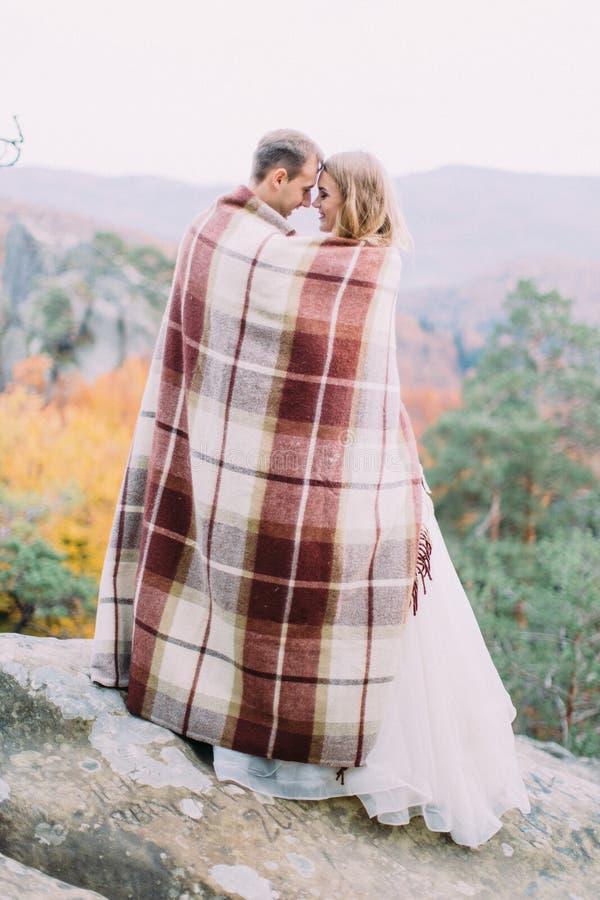 Foto integral del recién casado feliz envuelto en la tela escocesa hecha punto que se coloca en la roca imagen de archivo