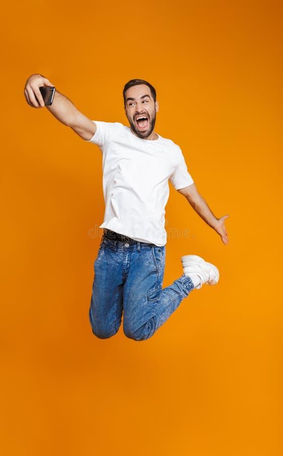 Foto integrale del tipo ottimista 30s nell'abbigliamento casual che ride e che prende selfie sul telefono cellulare, isolata sopr immagine stock libera da diritti
