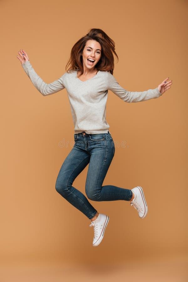 Foto integrale della giovane donna affascinante nel salto di abbigliamento casual fotografia stock