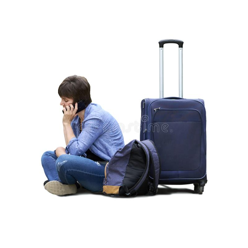 A foto isolada de uma mulher triste com uma bagagem senta-se na terra e em chamar o telefone imagens de stock