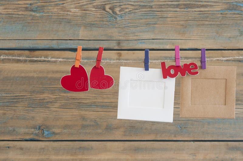 foto istantanee in bianco che appendono sulla corda da bucato con cuore rosso fotografia stock libera da diritti