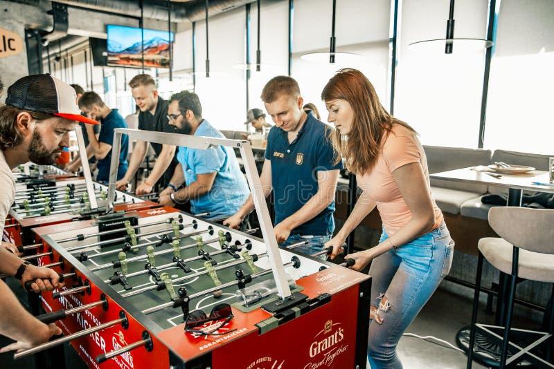 Foto KYIV, UKRAINA, stångliga av lån KickerKicker 10 Juni 2018 Aktiva män och kvinnor har gyckel under tabellfotbollleken royaltyfria foton