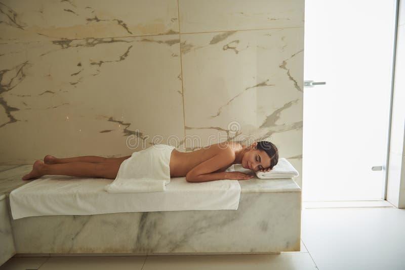 Foto lacónica de la señora joven que miente en la toalla en baño turco fotografía de archivo
