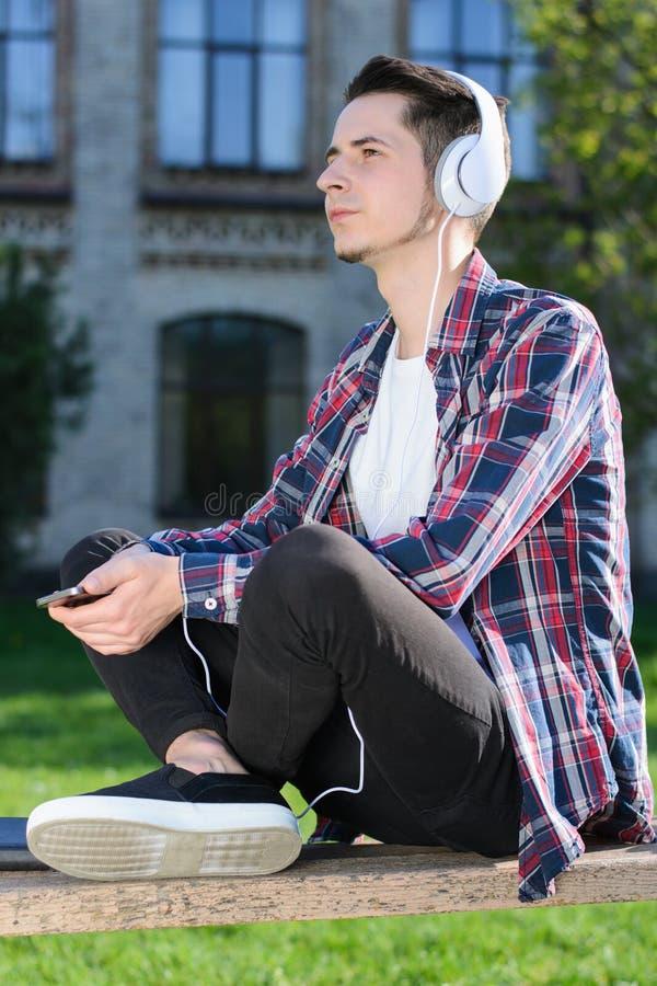 Foto laterale di profilo del tipo concentrato vago di sogno sicuro che ascolta la musica immagini stock