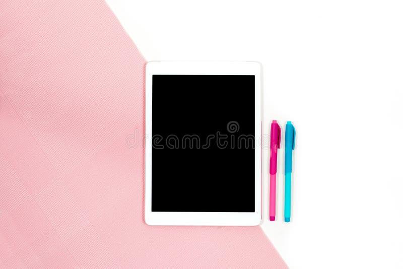 A foto lisa da configuração da mesa branca do escritório minimalistic com tabuleta e as penas azuis cor-de-rosa copiam o fundo do fotografia de stock