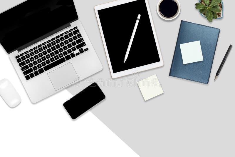 Foto lisa da configuração da tabela do escritório com laptop, a tabuleta digital, o telefone celular e os acessórios em um branco ilustração stock