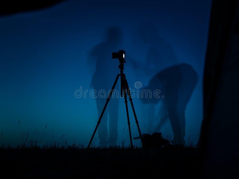 Foto longa artística da exposição de um fotógrafo na ação Silhuetas múltiplas e um tripé do un da câmera fotografia de stock royalty free