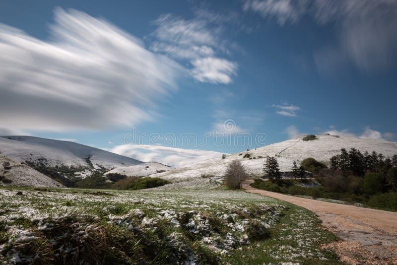 Foto lunga di esposizione di un paesaggio della montagna con erba verde e la m. immagine stock