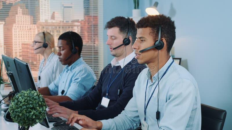 Foto média de agentes de call center multiracial conversando com os clientes no fone de ouvido fotografia de stock