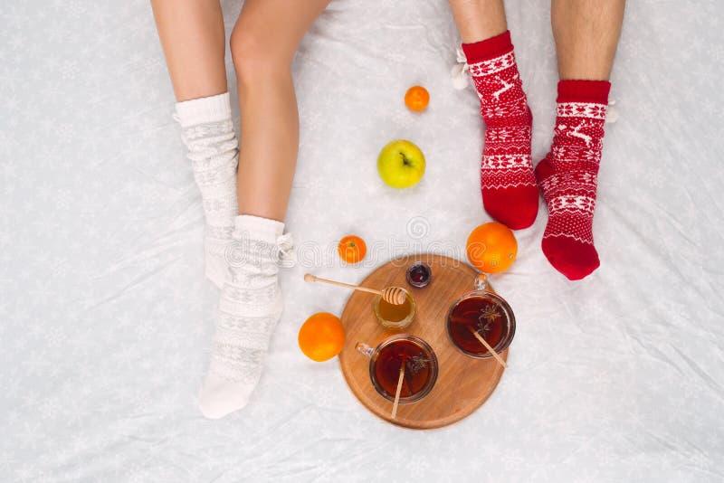 Foto macia da mulher e do homem na cama com chá e frutos, ponto de vista superior Pés fêmeas e masculinos em peúgas de lã mornas imagens de stock