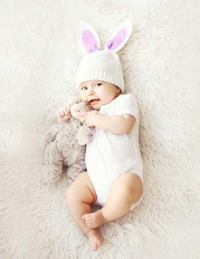 Foto macia do bebê bonito doce no chapéu feito malha com as orelhas de coelho fotografia de stock