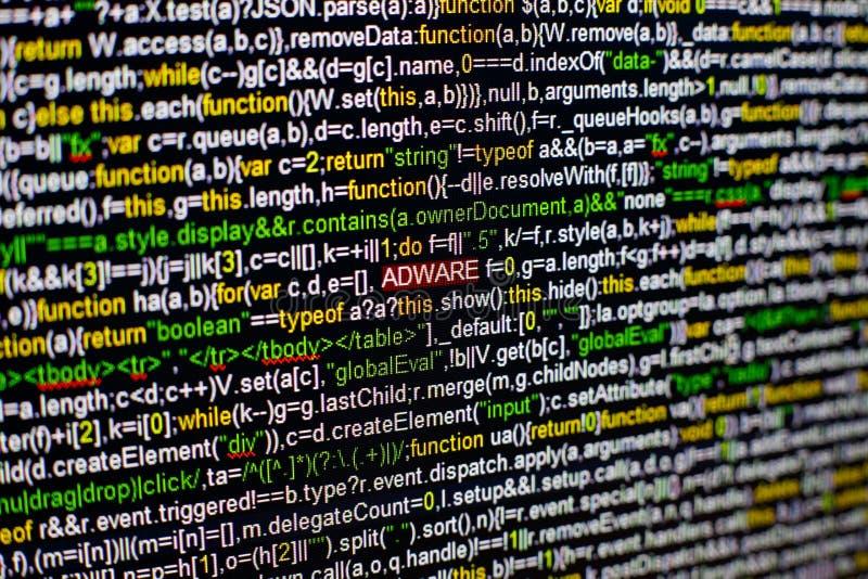 Foto macro do tela de computador com código fonte do programa e da inscrição destacada do ADWARE no meio Roteiro no foto de stock royalty free