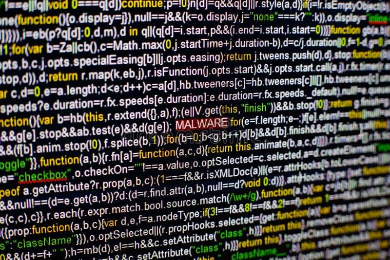 Foto macro do tela de computador com código fonte do programa e da inscrição destacada de MALWARE no meio Roteiro no imagens de stock