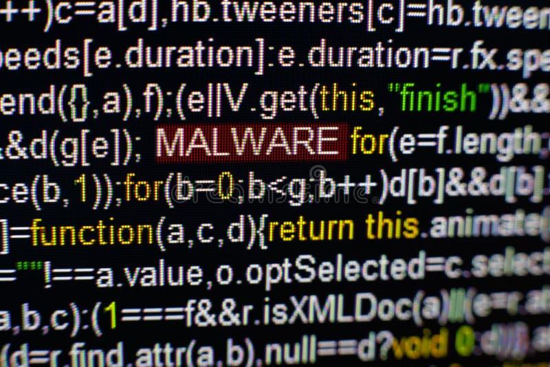 Foto macro do tela de computador com código fonte do programa e da inscrição destacada de MALWARE no meio Roteiro no fotos de stock