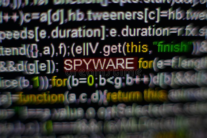 Foto macro do tela de computador com código fonte do programa e da inscrição destacada do SPYWARE no meio Roteiro no foto de stock