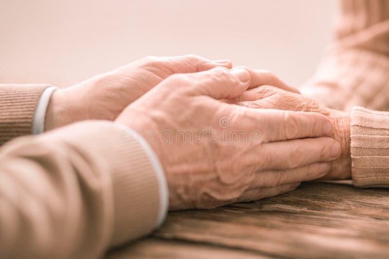Foto messa a fuoco sulle mani maschii che che sono vicino alla femmina immagine stock