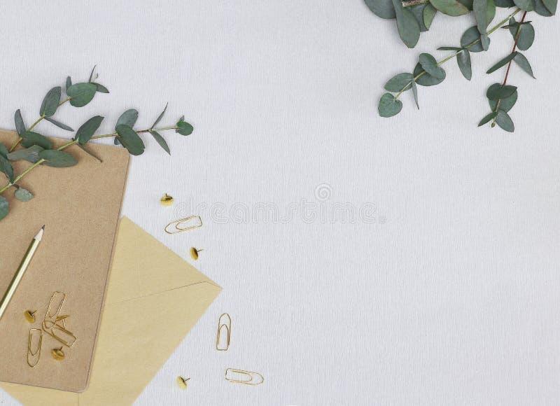 Foto minimalista con la matita dorata, graffette, perni, nota, busta, rami dell'eucalyptus fotografia stock