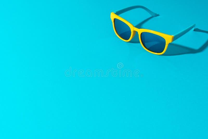 Foto minimalista degli occhiali da sole sul fondo del blu di turchese con lo spazio della copia immagine stock libera da diritti