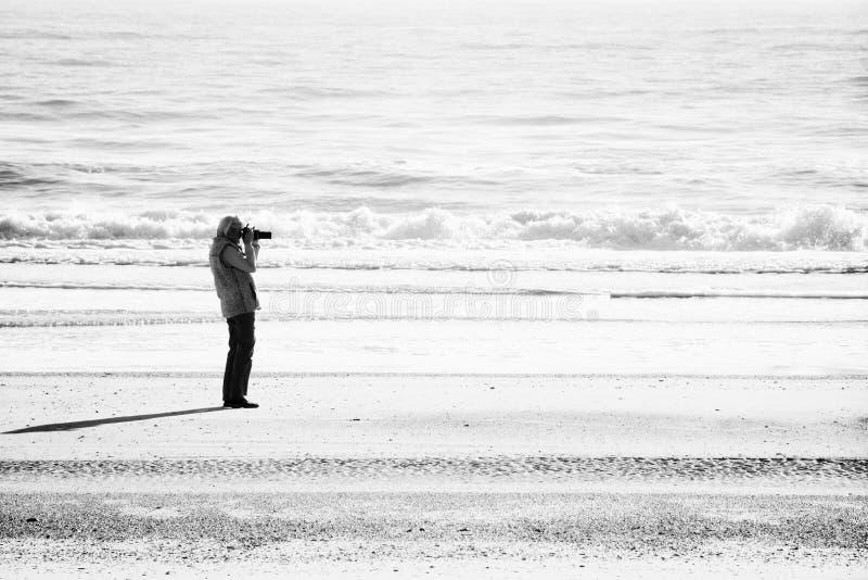 Foto minimalista preto e branco do tiro superior do fotógrafo da mulher em uma praia de Florida foto de stock