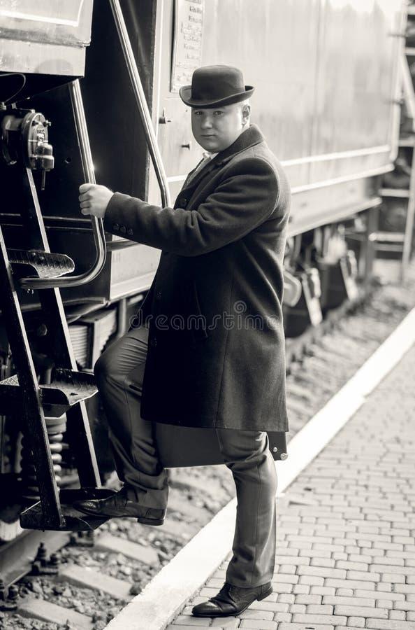 Foto monocromática do homem no chapéu de jogador que anda dentro do tr retro fotografia de stock